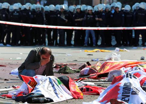 A man cries over the body of a victim, at the site of an explosion in Ankara, Turkey, Saturday, Oct. 10, 2015. (AP Photo/Burhan Ozbilici)