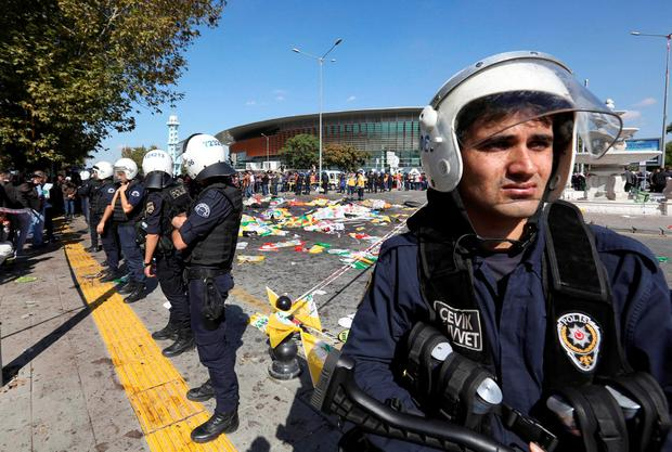 Turkish police officers secure the area at the site of an explosion, where the bodies of victims were covered with flags and banners (AP Photo/Burhan Ozbilici)