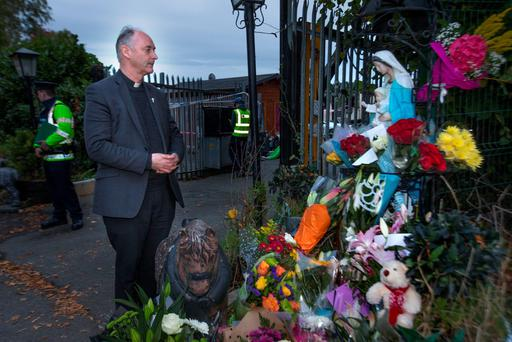 Fr. Derek Farrell, Parish Priest of the Parish of the Travelling Community looks at floral tributes at the scene of the tragic fire at Glenmaluck Road, Carrickmines Photo: Tony Gavin 10/10/2015