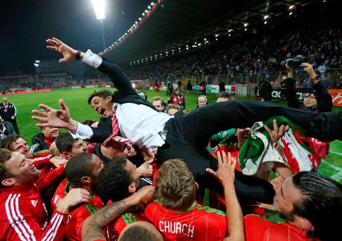 Wales manager Chris Coleman is held up by his players as they celebrate after qualifying for UEFA Euro 2016 Action Images via Reuters / Matthew Childs Livepic EDITORIAL USE ONLY.