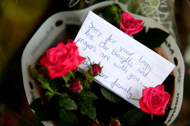 Flowers left at the scene in Carrickmines where ten people from two families, including a mother, father and a five-month-old baby, were killed in a fire yesterday Credit: Brian Lawless/PA Wire