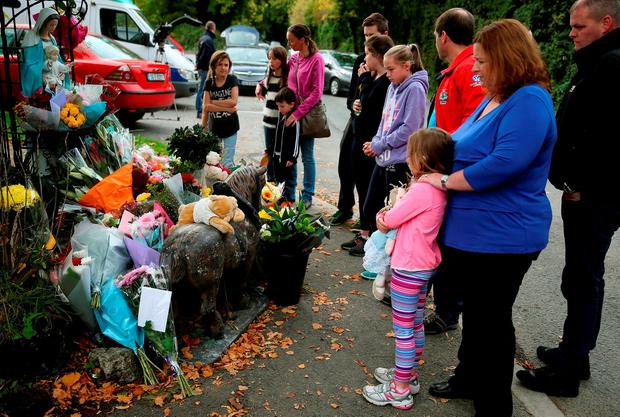 People gather as toys and flowers are left at a halting site for travellers in Carrickmines where ten people from two families were killed in a fire yesterday Credit: Brian Lawless/PA Wire