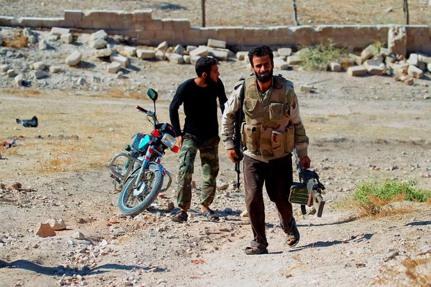 Rebel fighters carry their weapons as they head toward their positions in the town of Kafr Nabudah, in Hama province, Syria, on which forces loyal to Syria's President Bashar al-Assad are carrying out offensives to take control of the town, October 11, 2015. REUTERS/Ammar Abdullah