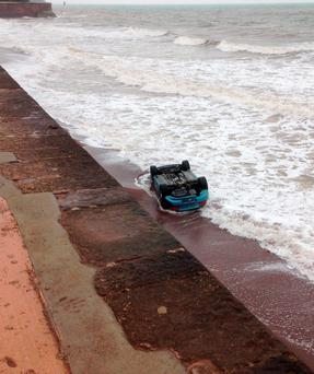 Handout photo issued by RNLI Teignmouth of a BMW Z3 convertible overturned as it crashed into the water near Teignmouth in Devon at around 8am. RNLI Teignmouth/PA Wire