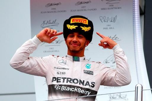 Lewis Hamilton swaps headgear as he celebrates his victory in the Russian Grand Prix yesterday