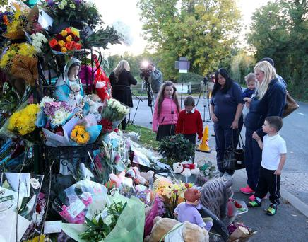 Mourners look at the floral tributes as they pay their respects at the scene in Glenamuck, Carrickmines