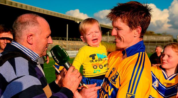 Clare hurling final man of the match, Niall Gilligan of Sixmilebridge, holds his son Michael (18 months)while being interviewed by Clare FM after the game