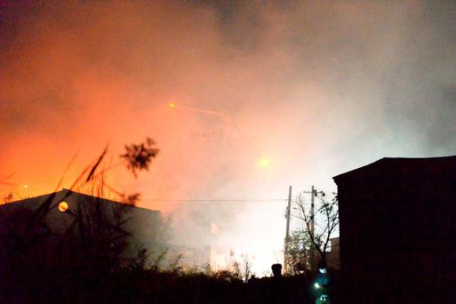 Fire and smoke rise at the site of an explosion at a warehouse in Beichen district in Tianjin