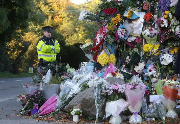A Garda looks at flowers laid in memory of those who died in the Carrickmines fire tragedy