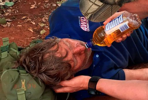 In this photo released by West Australia Police media unit, a West Australia Tactical Response Unit officer tends to Reginald George Foggerdy after he was found in an area about 170km east of Laverton, Western Australia