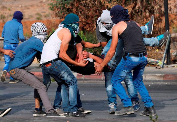 A wounded Palestinian protester is evacuated during clashes with the Israeli troops near the Jewish settlement of Bet El, near the West Bank city of Ramallah Credit: Mohamad Torokman (REUTERS)