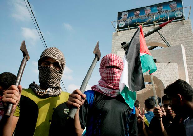 Palestinian students cover their faces with the trademark chequerred keffiyeh and hold up axes as a fellow protester waves a national flag during an anti-Israel protest Credit: SAID KHATIB (AFP/Getty Images)