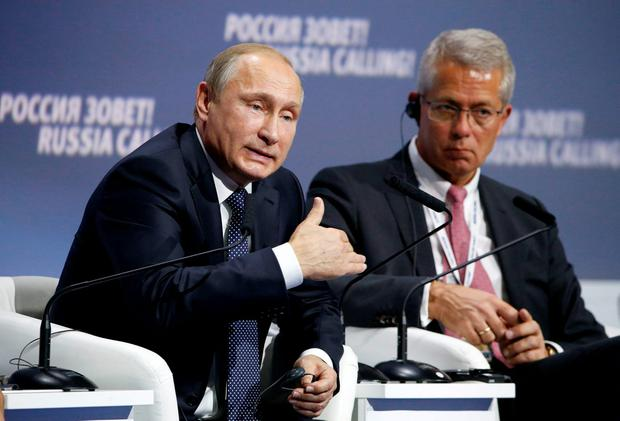Russian President Vladimir Putin, left, speaks at the 7th annual VTB Capital