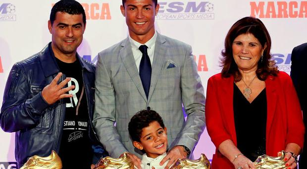 Real Madrid's striker Cristiano Ronaldo poses with his mother Dolores Aveiro (R), his son Cristiano Ronaldo Jr (C) and his brother Hugo (L) in front of his four Golden Boot trophies during a ceremony in Madrid