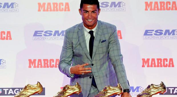 Real Madrid's striker Cristiano Ronaldo poses in front of his four Golden Boot trophies during a ceremony in Madrid last month