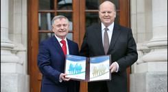 Minister for Public Expenditure and Reform, Brendan Howlin, and Minister for Finance, Michael Noonan, deliver the Budget on the steps of Government Buildings