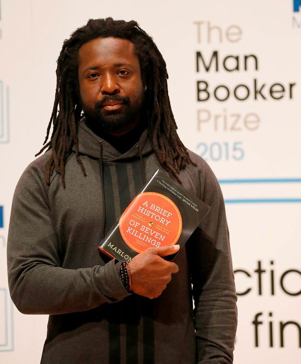Author Marlon James poses with his book 'A Brief History of Seven Killings' on stage at the Royal Festival Hall in London, Monday, Oct. 12, 2015