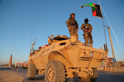 Afghan security personnel stand guard on an armoured vehicle at a checkpoint in Ghazni. Fighting flared in eastern Afghanistan as Taliban insurgents threatened to storm another provincial capital, two weeks after their lightning capture of northern Kunduz city which marked their biggest military victory in 14 years. AFP PHOTO / Rahmatullah Alizadah