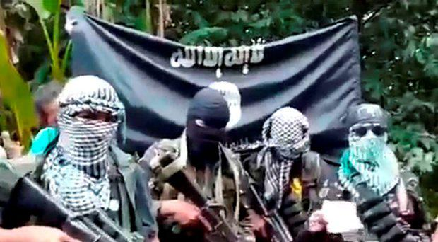 This undated image grab taken on October 13, 2015 from a video uploaded on YouTube shows gunmen standing behind three foreign men (not pictured) and a Filipina (not pictured) who were kidnapped last month in the southern Philippine