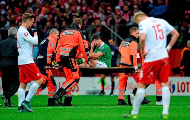 Shane Long, Republic of Ireland, is carried off on a stretcher after being injured in a tackle from Kamil Glik on Sunday evening