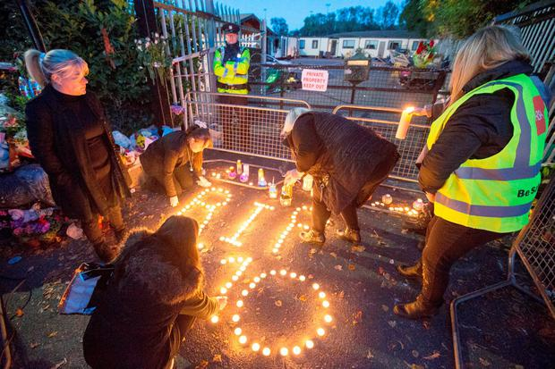 People gather to pay tribute to the ten victims of the Carrickmines fire at the Glenamuck Road Candle Lit Vigil.