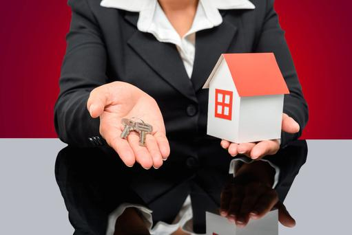 Business woman holding a model house and key