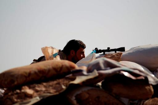 A Free Syrian Army fighter of the 101 Division takes a position behind sandbags near the town of Morek in the northern countryside of Hama, Syria October 14, 2015