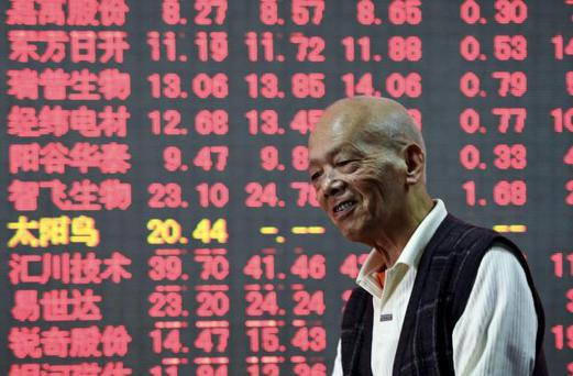 An investor smiles in front of an electronic board showing stock information at a brokerage house in Hangzhou, Zhejiang province, China, October 15, 2015. REUTERS/China Daily