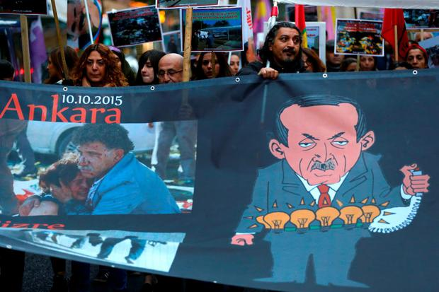 Demonstrators hold a banner depicting Turkish President Tayyip Erdogan (R) and bombing casualties, during a march to comemorate the victims of Saturday's bombing of an Ankara rally of pro-Kurdish activists and civic groups, through the streets of Frankfurt, Ocotber 14, 2015. REUTERS/Kai Pfaffenbach