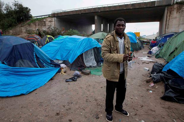 Sudanese migrant Muhammad poses in front of his tent in the