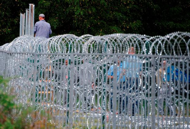 Prisoners of the Hungarian 'Csillag' technical unit preparing a new part of the iron fence at the Croatian-Hungarian border Credit: CSABA SEGESVARI (Getty Images)