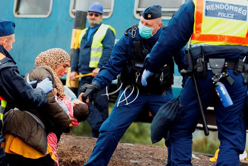 Hungarian policemen help migrants to board a train after they made their way through the countryside and crossed the Hungarian-Croatian border