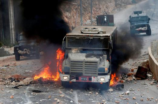 An Israeli military vehicle drives through burning tires during a raid in the West Bank