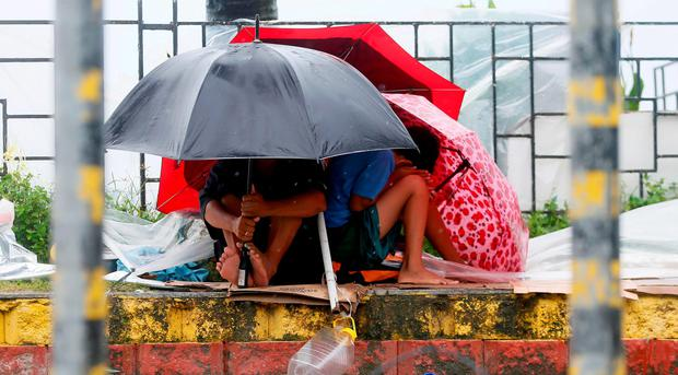 Residents huddle together under their umbrellas as strong winds and slight rain are brought by Typhoon Koppu Sunday, Oct. 18, 2015 in Manila, Philippines.