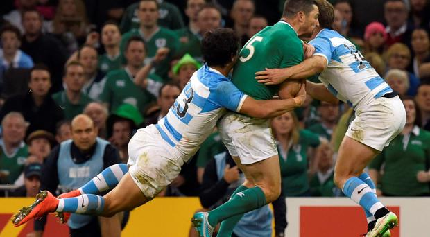 Ireland's full-back Rob Kearney (C) is tackled by Argentina's centre Matias Moroni (L) and Argentina's wing Santiago Cordero (R)