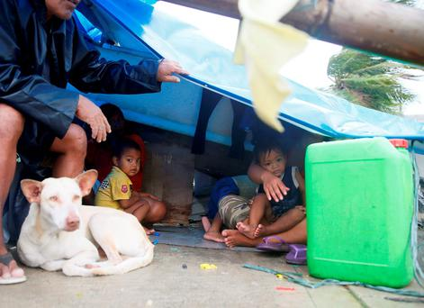 A family seeks shelter under a plastic sheet by a concrete wall amid strong wind and a slight rain brought by Typhoon Koppu. (AP Photo/Bullit Marquez)