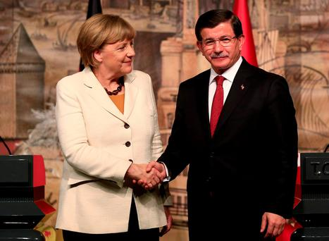 Turkish Prime Minister Ahmet Davutoglu shakes hands with Germany's Chancellor Angela Merkel following a joint news conference after their meeting at his office in Dolmabahce Palace in Istanbul.(AP Photo/Lefteris Pitarakis)
