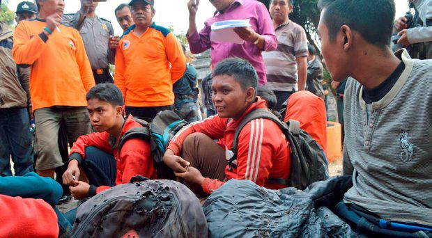 In this Sunday, Oct. 18, 2015 photo, hikers who managed to escape the forest fire on Lawu Mountain, rest upon arrival at Cemoro Sewu, East Java, Indonesia