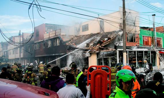 Firefighters put out a fire caused by the crash of a small plane on a bakery in Bogota Credit: El Tiempo newspaper