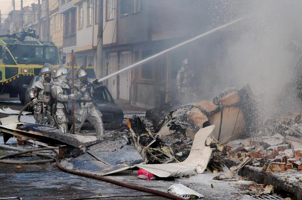 Firefighters spray water on a bakery set on fire after a small plane crashed into it in Bogota, Colombia (AP Photo/Santiago Cortez)