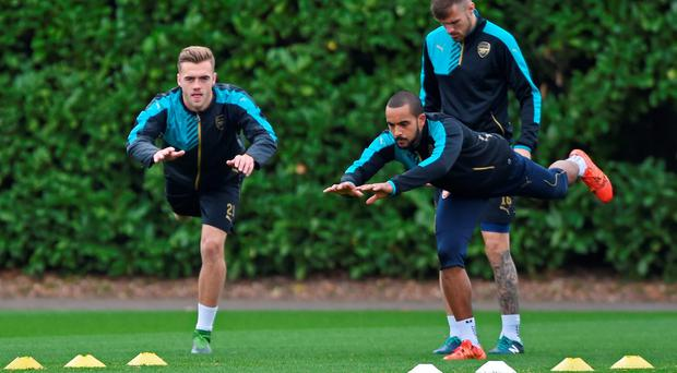 Aaron Ramsey and Theo Walcott go through their stretches during training yesterday