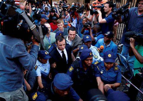 South African Olympic and Paralympic sprinter Oscar Pistorius leaves the North Gauteng High Court in Pretoria, in this September 12, 2014 file photo. REUTERS/Mike Hutchings/Files