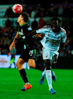 Bafetimbi Gomis of Swansea City is beaten to the ball by Philipp Wollscheid of Stoke City