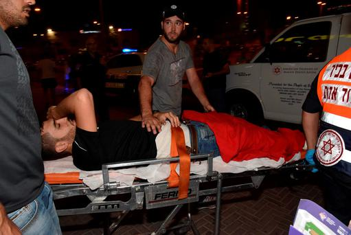 A wounded Israeli policeman is evacuated from the scene of an attack in Beersheba. Photo: AP