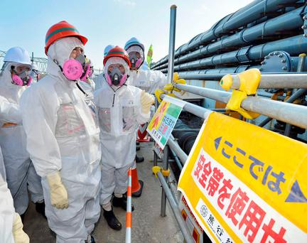 Japan's new Economy, Trade and Industry Minister Motoo Hayashi (2nd L), wearing a protective suit and a mask, inspects the Tokyo Electric Power Co. (TEPCO)'s tsunami-crippled Fukushima Daiichi nuclear power plant in Fukushima prefecture, in this photo taken and released by Kyodo October 12, 2015. Mandatory credit REUTERS/Kyodo ATTENTION EDITORS - THIS IMAGE HAS BEEN SUPPLIED BY A THIRD PARTY. FOR EDITORIAL USE ONLY. NOT FOR SALE FOR MARKETING OR ADVERTISING CAMPAIGNS. MANDATORY CREDIT. JAPAN OUT. NO COMMERCIAL OR EDITORIAL SALES IN JAPAN. THIS PICTURE IS DISTRIBUTED EXACTLY AS RECEIVED BY REUTERS, AS A SERVICE TO CLIENTS.