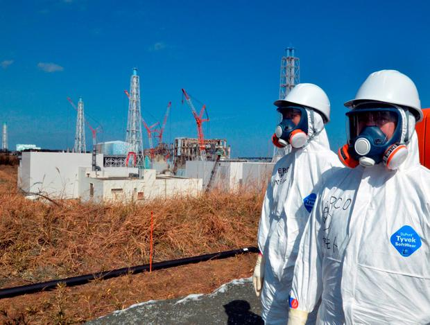 TEPCO workers standing before the stricken Fukushima Dai-ichi nuclear power plant at Okuma town in northern Japan Credit: Yoshikazu Tsuno (Getty Images)