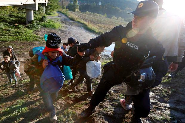 Migrants are helped up a steep muddy bank by police as they make their way on foot on the outskirts of Slovenia Credit: Srdjan Zivulovic (REUTERS)