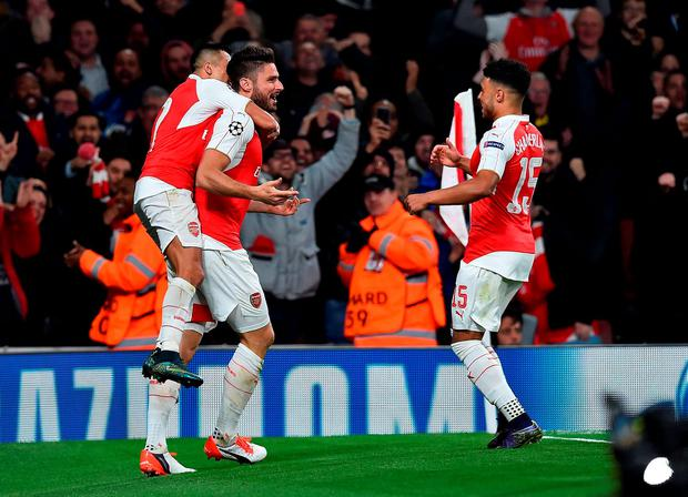 Arsenal's French striker Olivier Giroud (C) celebrates scoring his team's first goal with Arsenal's Chilean striker Alexis Sanchez (L) and Arsenal's English midfielder Alex Oxlade-Chamberlain during the UEFA Champions League football match between Arsenal and Bayern Munich at the Emirates Stadium in London, on October 20, 2015. AFP PHOTO / BEN STANSALLBEN STANSALL/AFP/Getty Images