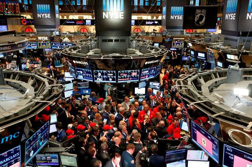 Traders crowd around a trading station for the Ferrari IPO near the opening of trading on the floor of the New York Stock Exchange. Photo: Reuters