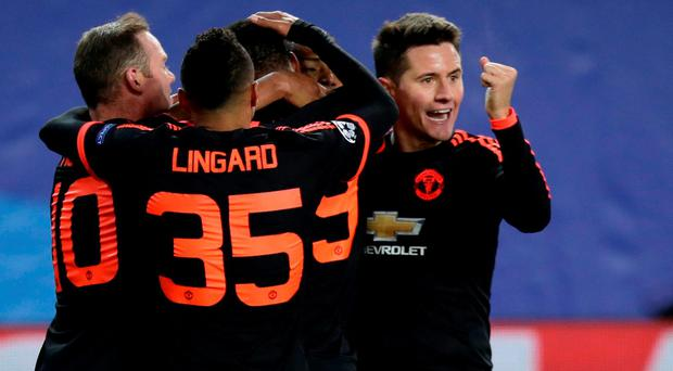 Manchester United's players celebrate around Anthony Martial after he scored an equalizer during the Champions League Group B soccer match between CSKA Moscow and Manchester United at the Arena Khimki stadium in Moscow